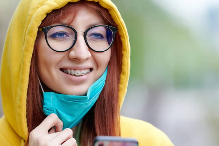 woman with braces smile with face mask for virtual invisalign and braces orthodontic consultations